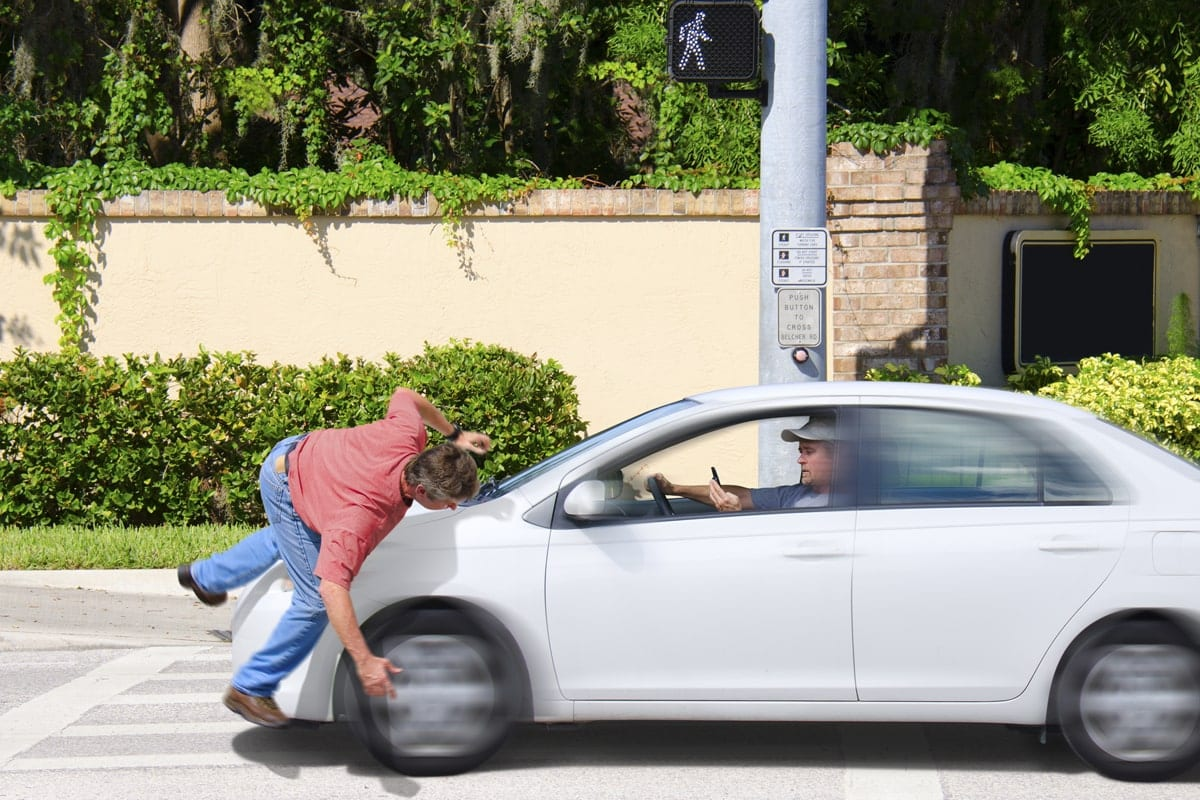 Guy texting and his a pedestrian with his car